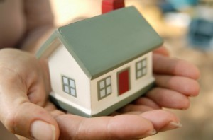Manos entregando una casa